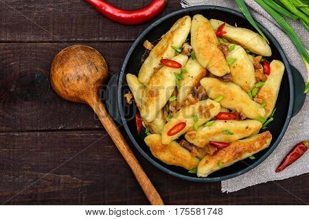 Popular traditional Czech Hungarian German dish: potato knedli (dumplings) with slices of fried bacon spicy red pepper and green onions. Serving on a cast iron pan. The top view