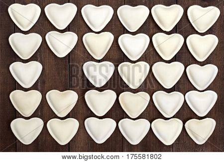 Uncooked dough in the shape of a heart (dumplings ravioli pelmeni) laid out in rows on a dark wooden background.
