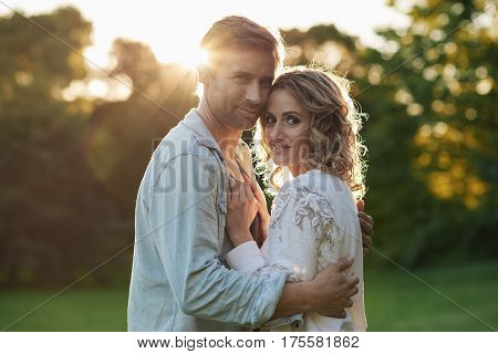 Portrait of an affectionate young couple embracing while enjoying a romantic sunny summer afternoon together in a park