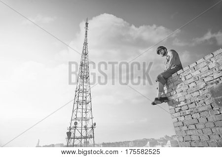 Brick wall. Monochrome low angle shot of a relaxed muscular shirtless builder sitting resting on top of brick wall observing the city copyspace sky summer relaxation rest masculinity fearless concept
