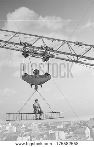Alone and calm. Black and white shot of a relaxed vintage handyman drinking milk sitting on a crossbar hanging from a construction crane high above the city relaxation peaceful calamity worker concept