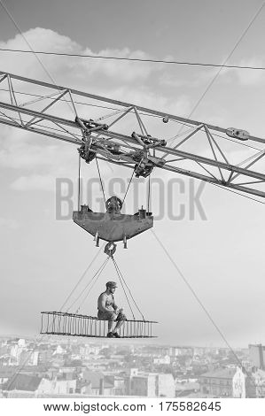 Away from city madness. Vertical monochrome shot of retro builder man relaxing having lunch sitting high above the city on a crossbar hanging from a construction crane worker industry business people