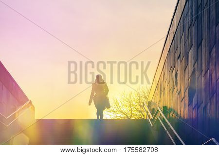 Blurred Abstract Background. Silhouette of a lonely woman climbing the stairs from an underpass. Concept of loneliness in city life