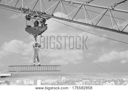 Muscular shirtless retro stressed and devastated builder standing on a crossbar hanging from construction crane above the city looking down with his hand to his head. copy space. failure concept.
