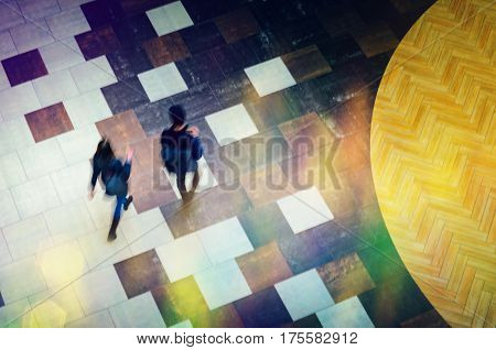 Blurred Abstract Background. Silhouettes of two people walking in a public building hall top view. Motion blur technique of low speed shot. Blur silhouettes of people's. Low speed shutter shot.
