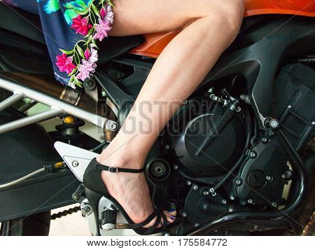 Woman in the short dress and stiletto-heeled shoes sitting on the motorcycle. Legs. Close-up.