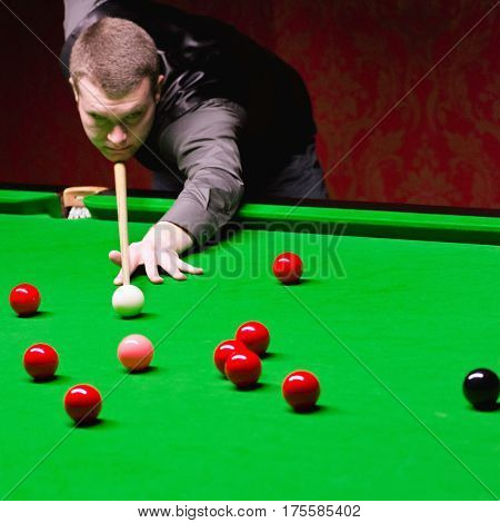 Professional snooker player taking a shot, color image , selective focus