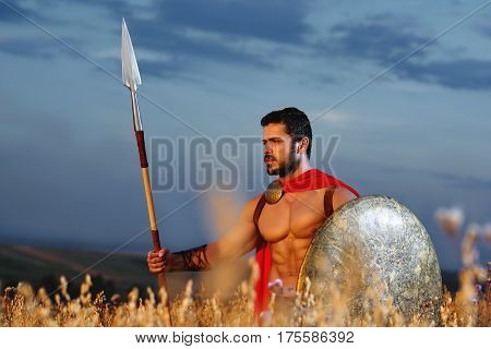 Powerful masculinity. Handsome young male Spartan warrior with stunning hot sexy muscular body standing confidently alone in the field with copyspace. Strength athletic physique hero protection concept.