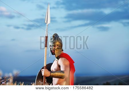 Legionary warrior in a helmet and battle dress standing alone holding a shield and a spear beautiful skyline on the background with copyspace. Bravery, masculinity and fearless fighter costume.
