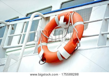 Red lifebuoy with rope on ship deck