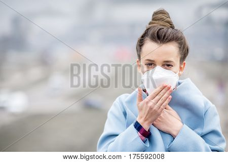 Young woman in protective mask feeling bad in the city with air pollution from traffic and manufacturing. Smog concept