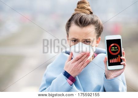 Woman in protective mask holding smart phone with air polution measurement of PM10 outdoors