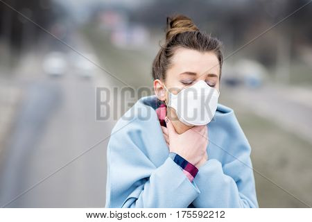 Young woman in protective mask feeling bad in the city with air pollution. Smog concept