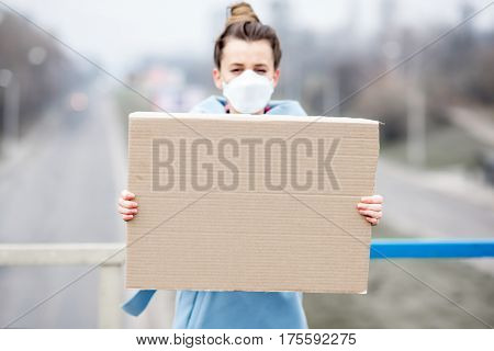 Young woman in protective mask from air pollution holding placard standing in the city