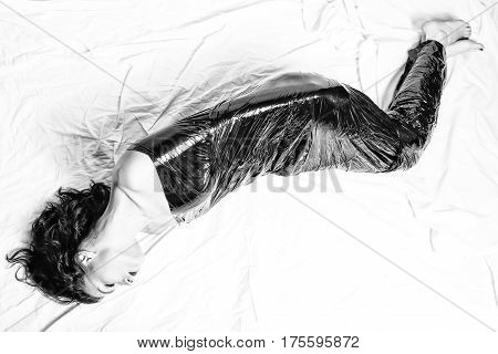 Depressed woman confined in foil. Black and white photo