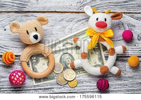 educational concept of sand pit bulls and bears in the financial market. crocheted rattle cow and bear children's toys among colorful beads. forex currency - us dollar banknotes and euro coins.