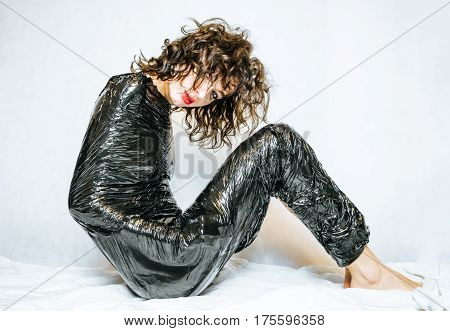 Sitting female in depression confined in black foil