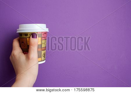 girl holding coffee to go against violet wal