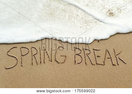 closeup of the text spring break written in the wet sand of the seashore, in a quiet beach