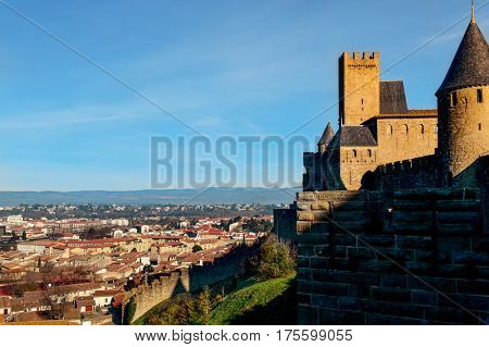 a view of the walls and towers of the Cite de Carcassonne, in Carcassone, France, on the right, and the new city on the left