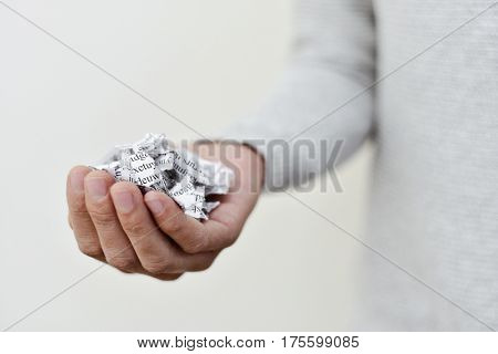 closeup of a young caucasian man with a printed letter or document broken into a thousand pieces in his hand