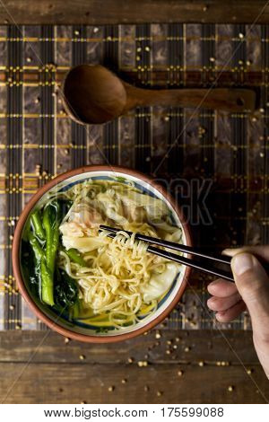 closeup of a young man getting some noodles with his chopsticks from an earthenware bowl with shrimp wonton noodle soup with choy sum, placed on a table set for lunch or dinner poster