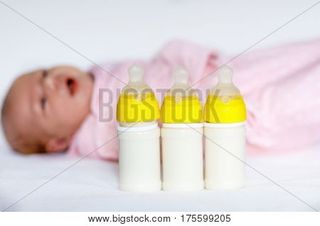 Adorable newborn baby girl with nursing bottles. Formula drink for babies. New born child, little girl laying in bed. Family, new life, childhood, beginning, bottle-feeding concept.