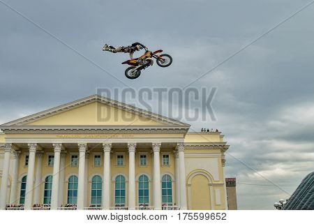 Tyumen Russia - June 10 2009: Red Bull X-Fighters Exhibition Tour. Freestyle Motocross. Sportsman carries out a trick over city Drama theater background
