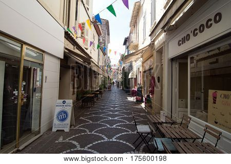 Antibes France - June 27 2016: day view of Rue Fourmilliere with shops in Antibes France.