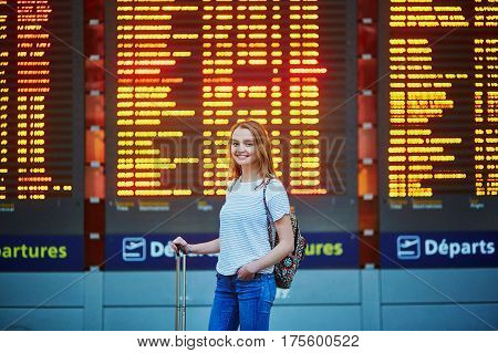 Tourist Girl With Backpack And Carry On Luggage In International Airport, Near Flight Information Bo