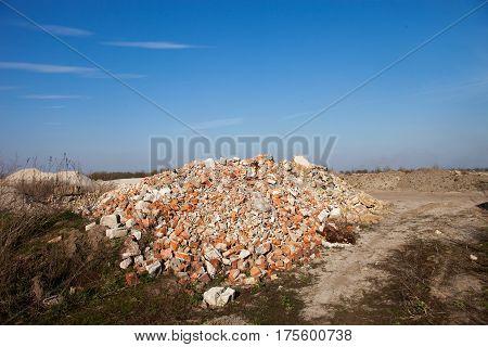 Pile of broken bricks near the road. Construction debris.