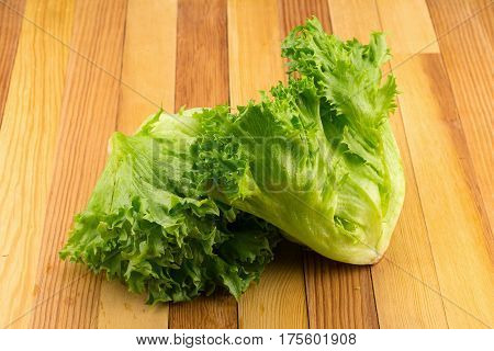 green frillies iceberg lettuce on wooden table.