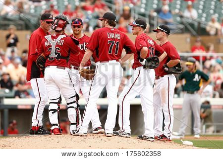 SCOTTSDALE, AZ-MAR 6: Arizona Diamondbacks pitching coach Mike Harkey (L) speaks with team against the Oakland Athletics at Salt River Fields at Talking Stick on March 6, 2014 in Scottsdale, Arizona.