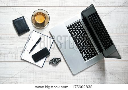 View of a wooden table with a laptop, mobile, notebook, watch, wallet, pen and a cup of coffee on it
