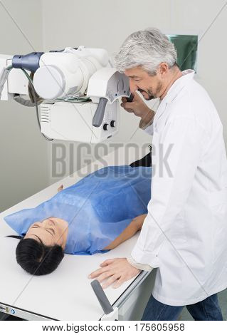 Radiologist Adjusting X-ray Machine Over Woman Patient