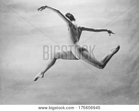 Young beautiful modern style dancer jumping on a studio background. Colorless image