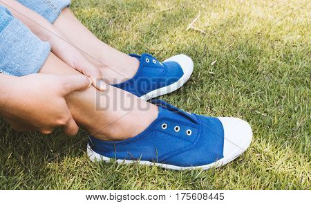 Woman hand holding for ankle pain in park health care and medical concept vintage tone