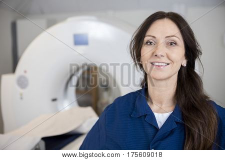 Smiling Female Professional Against MRI Machine In Hospital