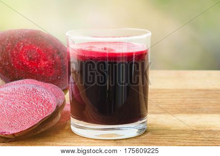 Fresh beet juice in glass and sliced beetroot on wooden table blur defocused nature background