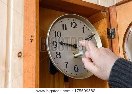 The mechanical watch is hanging on the wood wall. The man winds the clock with a key.