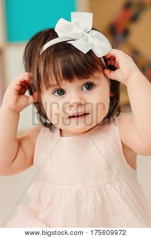 vertical close up indoor portrait of cute happy baby girl playing with dressy white headband with bow