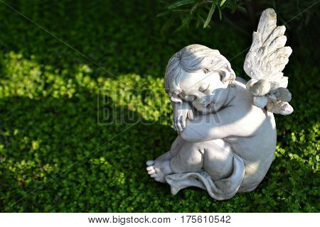 Little angel figurine sitting on the grave