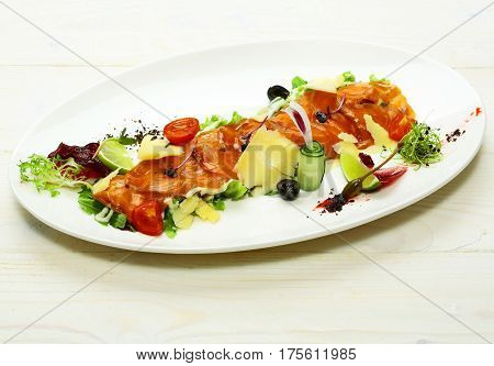 Delicious red fish or salmon fillet slices sashimi garnished with cheese and colorful vegetables on plate on white background. Modern molecular gastronomy