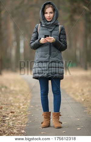 Outdoor portrait of beautiful thoughtful young woman wearing coat with hood texting on her smartphone posing in forest spring park. Toned effect