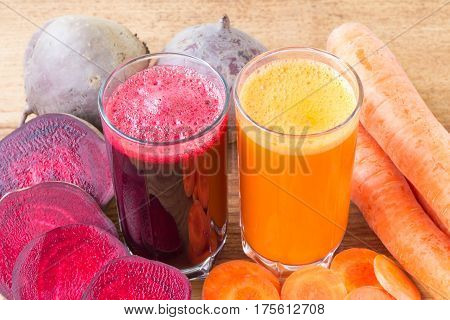 Two glass of fresh beet and carrot juice beetroot and carrots vegetable on wooden table