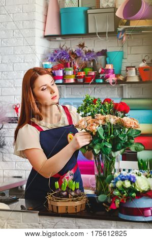 attractive young girl working in a flower shop,