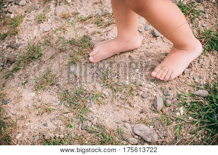 Little Girl Barefoot Closeup Of A Foot On A Natural Background.