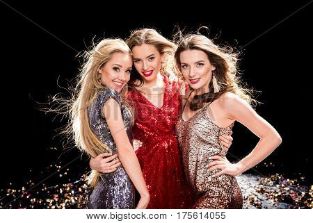 Three young stylish women at the party smiling and looking at camera