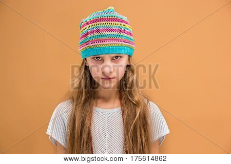 Angry young girl in hat looking at camera with hate on brown studio background