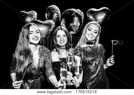 Young women holding champagne glasses and party sticks black and white photo